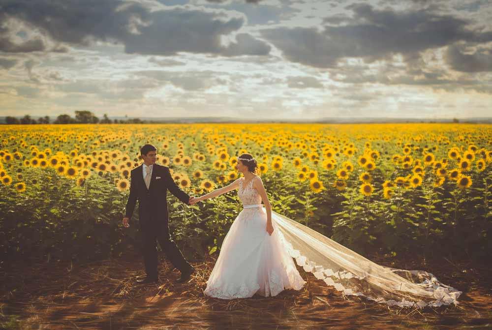 Una coppia appena sposata che si tiene per mano in un campo di girasoli